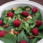 Salad of arugula, spinach, almonds, and raspberries with yogurt sauce