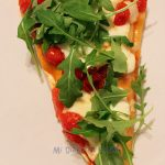 Pizza with mozzarella, caramelized cherry tomatoes and arugula