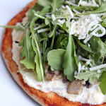 Pizza with ricotta, caramelized onions, mushrooms, and arugula
