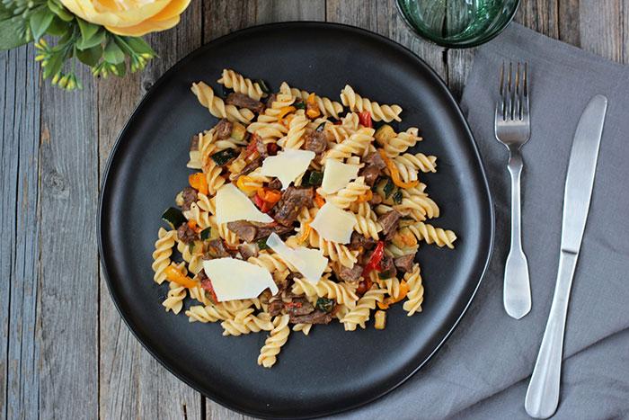 Pasta con carne y vegetales salteados